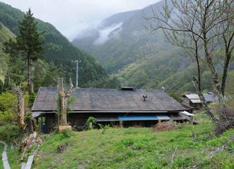 南アルプストンネル工事の最前線となる大鹿村釜沢地区。3000メートル級の山々を望む急な斜面に、民家が建つ。