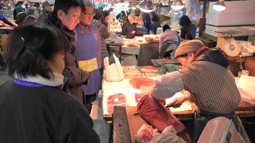 客と会話しながら、包丁を入れる(2016年12月31日、椿魚市場)